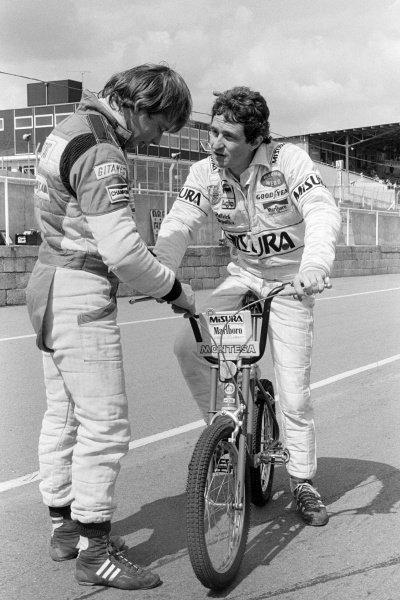 Patrick Depailler (FRA) Alfa Romeo (Right) on his BMX bike, talks with Didier Pironi (FRA) Ligier. Formula One Testing, Brands Hatch, England, 19 June 1980.