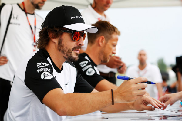 Hungaroring, Budapest, Hungary. Thursday 23 July 2015. Fernando Alonso, McLaren, and Jenson Button, McLaren, sign autographs for fans. World Copyright: Charles Coates/LAT Photographic ref: Digital Image _J5R0895