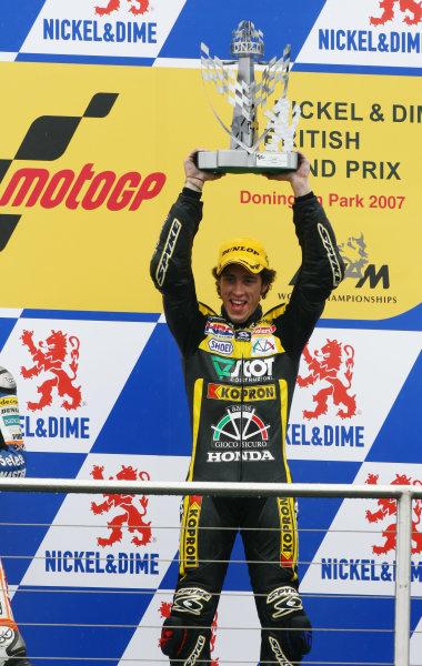 2007 MotoGP. British Grand Prix.  Donington Park, England. 22nd-24th June 2007.  250cc. Andrea Dovizioso, Honda, 1st position, celebrates with the trophy on the podium.  Ref: IMG_5945a. World Copyright: LAT Photographic