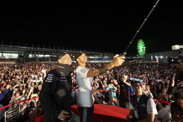 Valtteri Bottas, Mercedes AMG F1, and Lewis Hamilton, Mercedes AMG F1, take a photo with the crowd from the stage