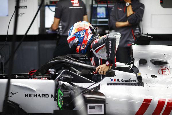 Romain Grosjean, Haas F1 Team, enters his cockpit in the team's garage.