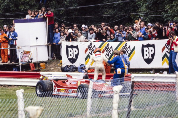 Gilles Villeneuve steps out of his Ferrari 312T5 with assistance from marshals.