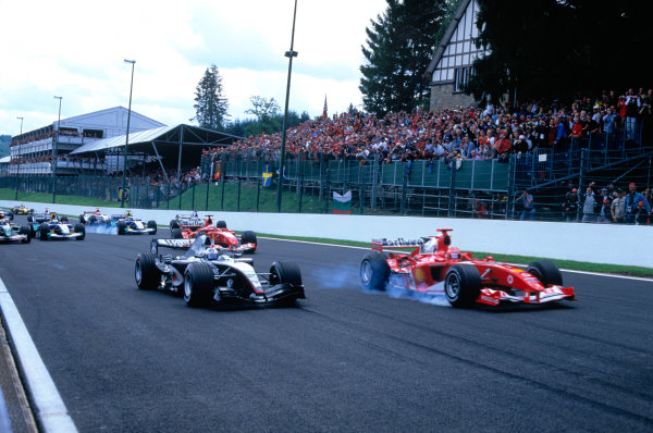 2004 Belgian Grand Prix. Spa Francorchamps, Belgium. 27th - 29th August. Michael Schumacher, Ferrari F2004 locks a front wheel as David Coulthard, McLaren Mercedes MP4/19B overtakes goung into turn one at the start of the race. Action.  World Copyright:LAT Photographic Ref:35mm Image A20
