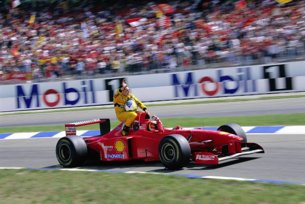 Michael Schumacher, Ferrari F310B, gives Giancarlo Fisichella a lift back to the pits.