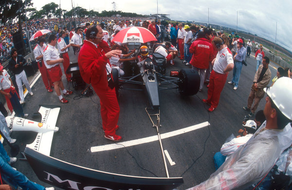 1991 Brazilian Grand Prix.Interlagos, Sao Paulo, Brazil.22-24 March 1991.Ayrton Senna (McLaren MP4/6 Honda) sits in pole position on the grid, with team boss Ron Dennis and chief designer Neil Oatley in front.Ref-91 BRA 12.World Copyright - LAT Photographic