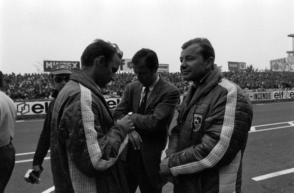Porsche Designer, Ferdinard Piech and Porsche press officer, Rico Steinemann in the suit check the time on their watches.