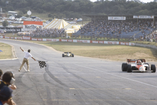 Niki Lauda, McLaren MP4-2 TAG, crossing the line and taking the chequered flag, leading Derek Warwick, Renault RE50.
