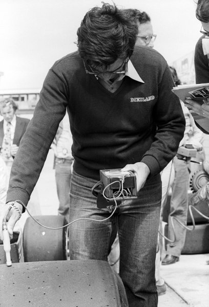 A Michelin tyre technician checks the temperature of a tyre on a Ferrari 312T3 in the pits.