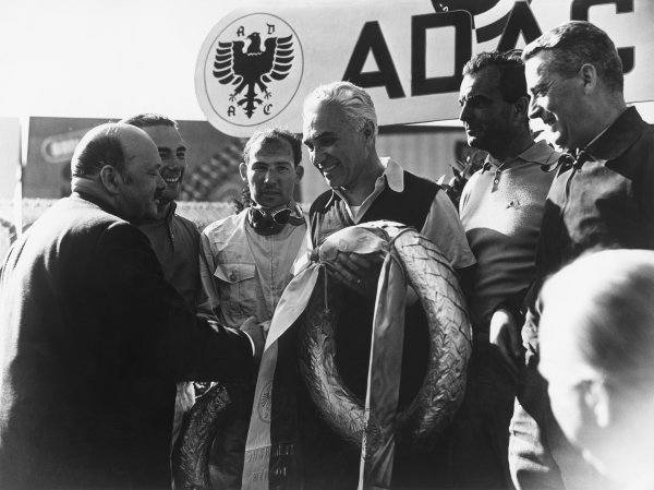 Nurburgring, Germany. 27th May 1956 Jules Kother, Sports President of the ADAC, congratulates Piero Taruffi, Harry Schell, Stirling Moss and Jean Behra, Maserati 300S, on the podium, 1st position, portrait. World Copyright: LAT Photographic Ref: Autocar glass Plate C46373.