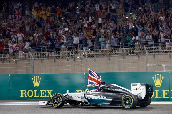 Yas Marina Circuit, Abu Dhabi, United Arab Emirates. Sunday 23 November 2014. Lewis Hamilton, Mercedes F1 W05 Hybrid, 1st Position, drives back to Parc Ferme with his flag raised. World Copyright: Alastair Staley/LAT Photographic. ref: Digital Image _79P0848
