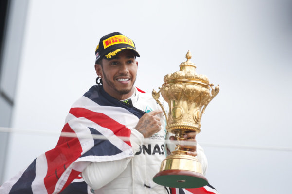Race winner Lewis Hamilton, Mercedes AMG F1 celebrates on the podium with the trophy and with a flag