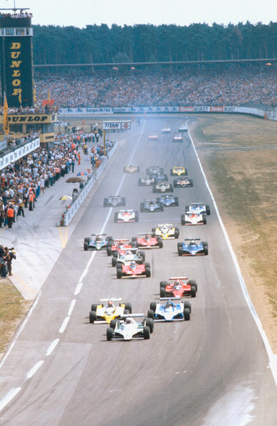 1979 German Grand Prix.Hockenheim, Germany.27-29 July 1979.Alan Jones (Williams FW07 Ford) leads Jean-Pierre Jabouille (Renault RS10), Jacques Laffite (Ligier JS11 Ford) and Nelson Piquet (Brabham BT48 Alfa Romeo) into the Nordkurve at the start. Ref-79 GER 01.World Copyright - LAT Photographic