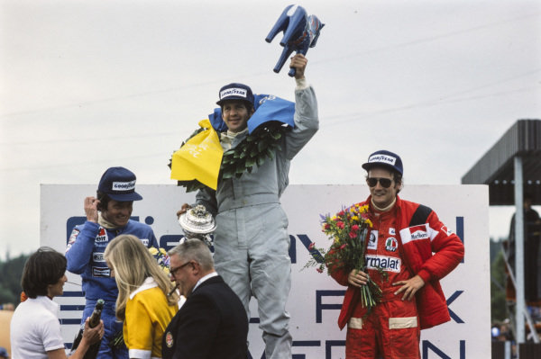 Jody Scheckter celebrates victory with teammate Patrick Depailler, 2nd position, and Niki Lauda, 3rd position.