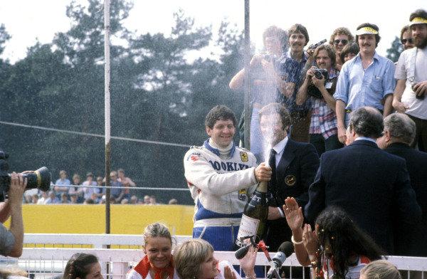 Jody Scheckter sprays champagne on the podium, celebrating his victory.
