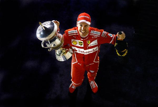 Bahrain International Circuit, Sakhir, Bahrain.  Sunday 16 April 2017. Sebastian Vettel, Ferrari, celebrates with his trophy and chanpagne after winning the race. World Copyright: Steven Tee/LAT Images ref: Digital Image _R3I0548