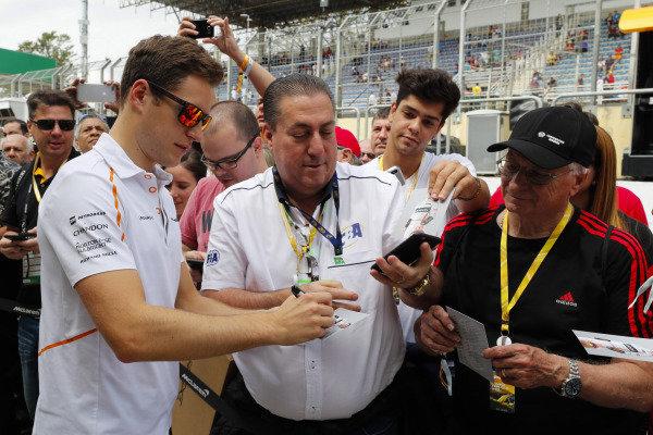 Stoffel Vandoorne, McLaren, signs autographs for fans.