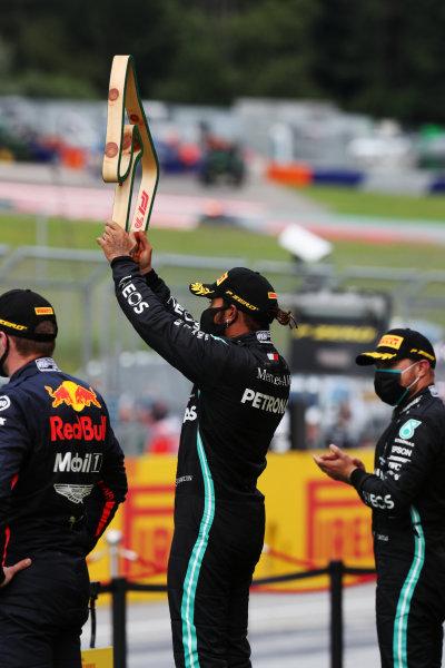 Winner Lewis Hamilton, Mercedes-AMG Petronas F1 raises his trophy on the podium ahead of Valtteri Bottas, Mercedes-AMG Petronas F1 and Max Verstappen, Red Bull Racing