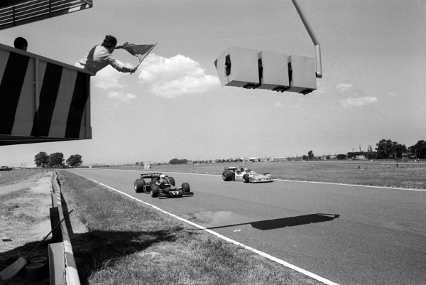 A marshal waves a flag at Renzo Zorzi (ITA) Shadow DN5B (Left) and Ian Scheckter (RSA) March 761B.Argentinean Grand Prix, Rd1, Buenos Aires, Argentina, 9 January 1977.