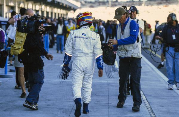 Juan Pablo Montoya walks down the pitlane.