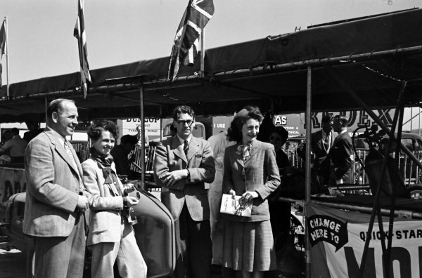Reg Parnell and Bob Gerard with their wives in the pits.