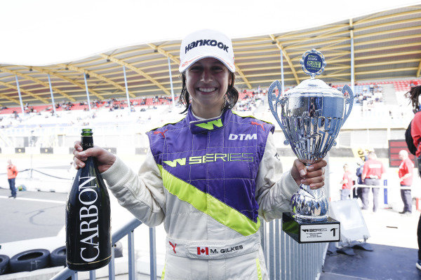 Megan Gilkes (CAN) celebrates with champagne and trophy