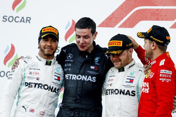Lewis Hamilton, Mercedes AMG F1, the Mercedes Constructors trophy delegate, Valtteri Bottas, Mercedes AMG F1, 1st position, and Sebastian Vettel, Ferrari, 3rd position, on the podium